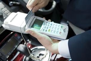 タクシー運賃をカード精算する運転手の手元の素材 [FYI00912738]