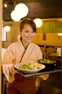 居酒屋で料理を運ぶ女性の素材 [FYI00912751]