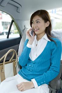 タクシーの中で電話する女性の素材 [FYI00912760]