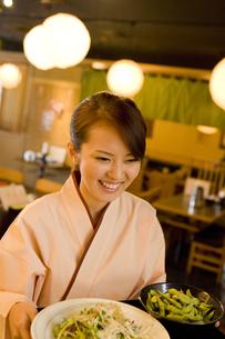 居酒屋で料理を運ぶ女性の素材 [FYI00912766]