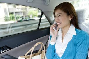 タクシーの中で電話する女性の素材 [FYI00912800]