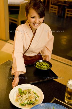 居酒屋で料理を運ぶ女性の素材 [FYI00912821]