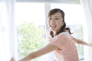 カーテンを開ける笑顔の女性の素材 [FYI00913339]