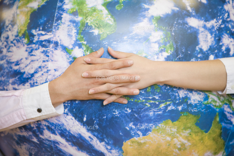 地球を握る男女の手元の素材 [FYI00913645]