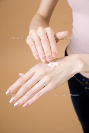 化粧品を塗ろうとする女性の手の素材 [FYI00915374]