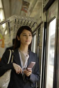 電車内で携帯電話を手に立っている女性の素材 [FYI00916519]