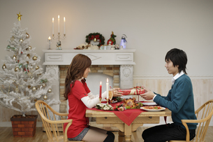 男性にクリスマスプレゼントを渡す女性の素材 [FYI00916526]