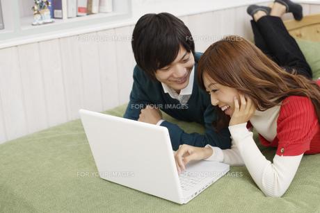 寝そべりながらパソコンを見ているカップルの素材 [FYI00916535]