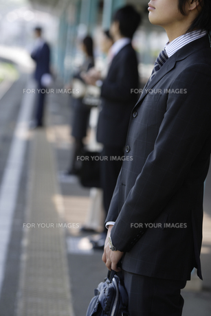 駅のホームで電車を待つビジネスマンの素材 [FYI00916538]