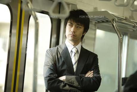電車内で腕組みをして立つ男性の素材 [FYI00916554]