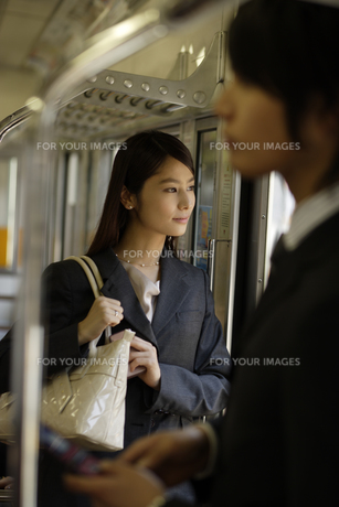 電車内から外の風景を見るOLの素材 [FYI00916565]