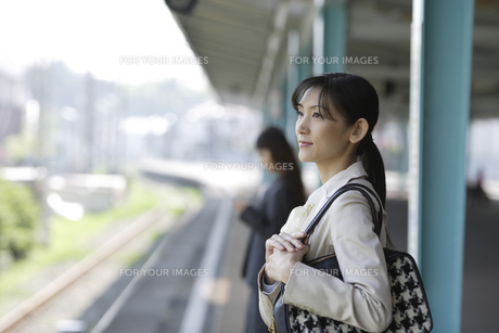 駅のホームで電車待ちをする女性の素材 [FYI00916569]