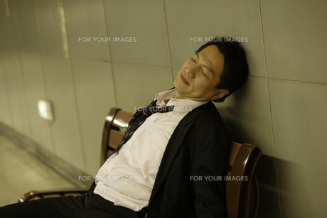 ベンチで居眠りをするビジネスマンの素材 [FYI00916578]