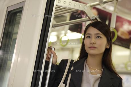 電車内から外の風景を見るOLの素材 [FYI00916585]