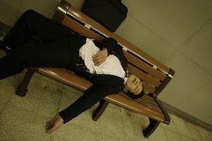 ベンチで居眠りをするビジネスマンの素材 [FYI00916590]