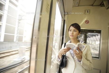 電車内から外の景色を見るOLの素材 [FYI00916600]