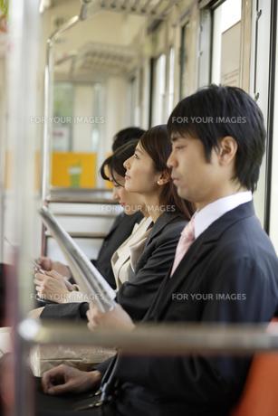 電車内の座席に座るビジネスマンとOLの素材 [FYI00916603]