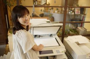 コピー機の前に立ちこちらを見る女性の素材 [FYI00916605]