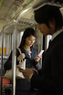 電車内で携帯電話を見ているOLの素材 [FYI00916612]