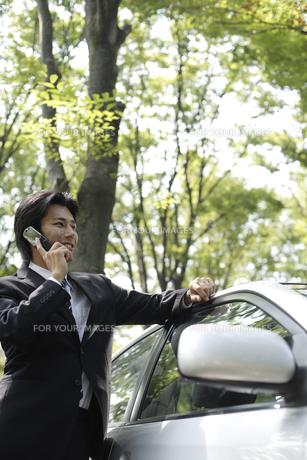 車の傍に立って携帯電話で会話する男性の素材 [FYI00916624]
