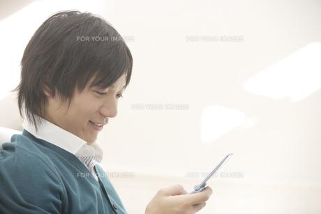 携帯電話を見ている男性の素材 [FYI00916629]