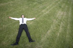 芝生の上に寝転がるビジネスマンの素材 [FYI00916643]