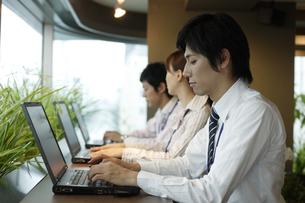 並んでパソコンをしている3人の男女の素材 [FYI00916662]