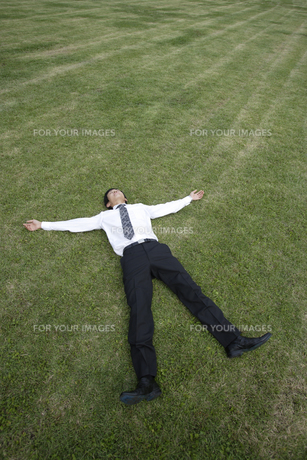 芝生の上に寝転がる男性の素材 [FYI00916693]