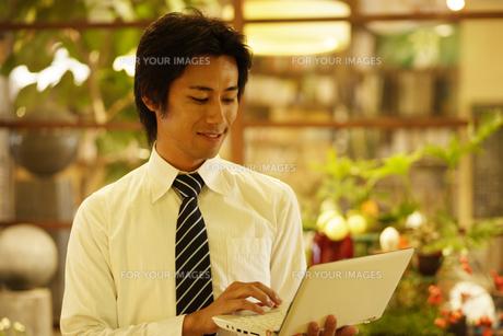 手に持ったパソコンを操作する男性の素材 [FYI00916709]