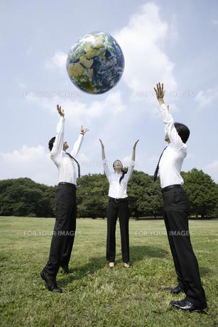 地球ボールを投げ上げるビジネスマンたちの素材 [FYI00916716]