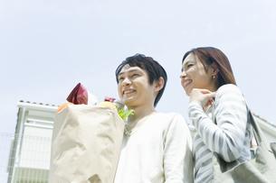 買い物袋を抱えた笑顔のカップルの素材 [FYI00916914]