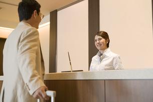 フロントに来た男性客を笑顔で迎える従業員の素材 [FYI00917865]