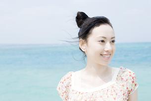 青い海を背に笑顔を見せる女性の素材 [FYI00917988]