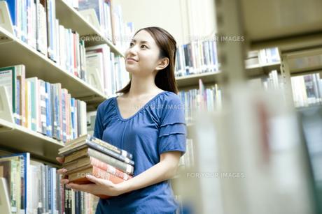 図書室で本を抱える女子学生の素材 [FYI00918233]
