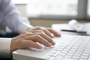 パソコンのキーボードを打つ男性の手元の素材 [FYI00918250]