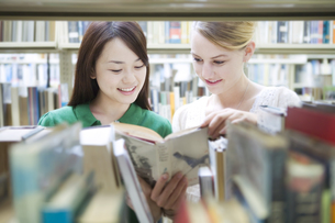図書室で本を見るふたりの女子学生の素材 [FYI00918307]