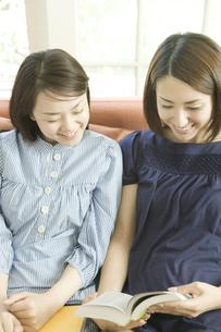 笑顔で本を見るふたりの女性の素材 [FYI00918379]