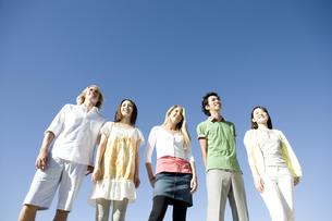 青空を背に並んで立つ若者たちの素材 [FYI00918682]