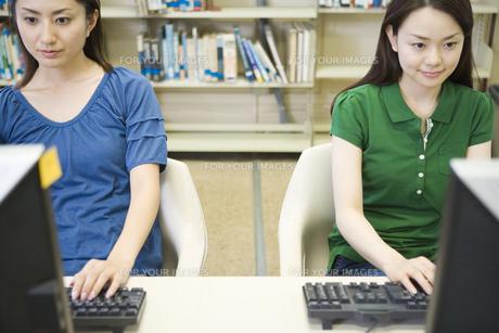 図書室でパソコンをする女子学生の素材 [FYI00918847]
