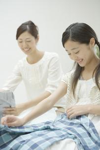 洗濯物をたたむ母と娘の素材 [FYI00919267]