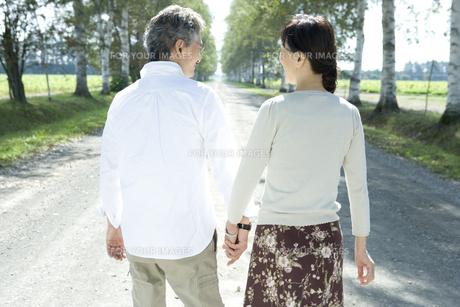 手をつないで歩くシニア夫婦の後姿の素材 [FYI00919293]