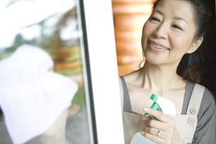 窓拭きをするシニア女性の素材 [FYI00919306]