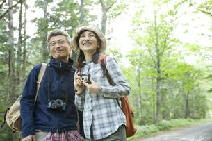 緑の中でカメラを持ったシニア夫婦の素材 [FYI00919375]