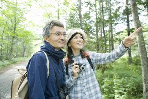 緑の中でカメラを持ったシニア夫婦の素材 [FYI00919419]