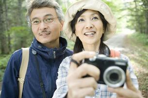 緑の中でカメラを持ったシニア夫婦の素材 [FYI00919450]