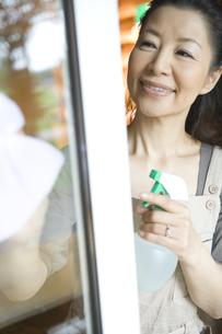 窓拭きをするシニア女性の素材 [FYI00919464]
