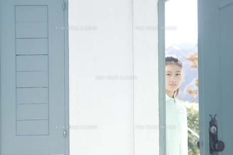 扉の隙間から顔を出す日本人の女の子の素材 [FYI00920142]