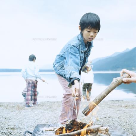 湖畔でおこした焚火のそばで遊ぶ4人の男の子の素材 [FYI00920383]