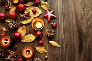 金色の枯葉とキャンドルとクリスマスオーナメント 赤色系 黒木材背景の写真素材 [FYI00920439]