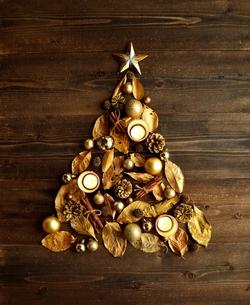 金色の枯葉のクリスマスツリーとキャンドル 黒木材背景の写真素材 [FYI00920455]